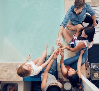 Group of friends toasting at poolside party