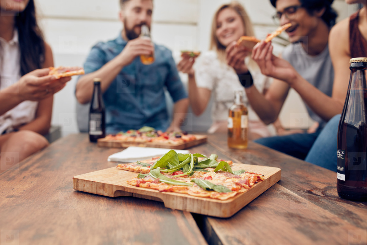 Pizza on table with friends enjoying party