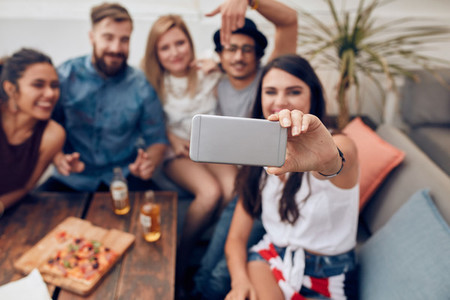 Group of young people taking selfie at party
