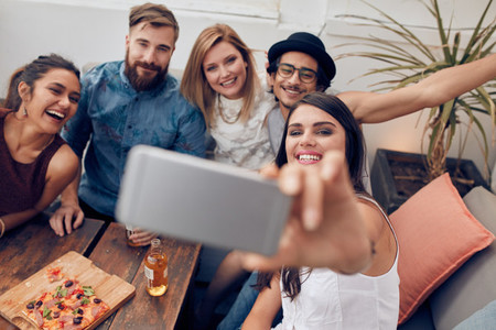 Multiracial people having fun at party taking a selfie