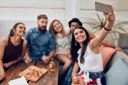 Happy and joyful young people taking selfie at party