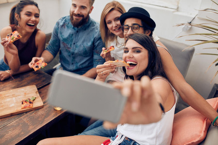 Young people taking a selfie while eating pizza