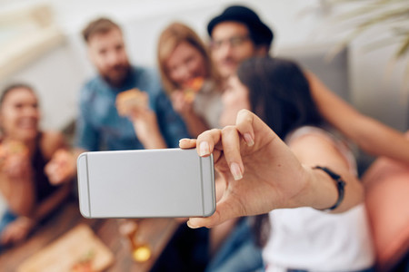 Woman taking a selfie at party with friends
