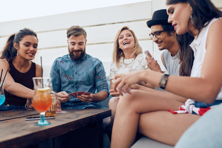 Young people partying together and playing cards