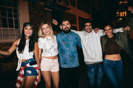 Group of cheerful people in a rooftop party at night