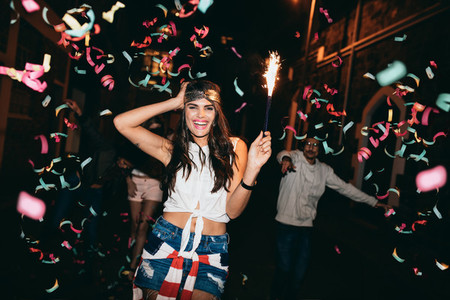 Friends partying outdoors with confetti and sparklers