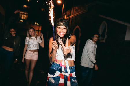 Cheerful young woman holding a sparkler enjoying in party