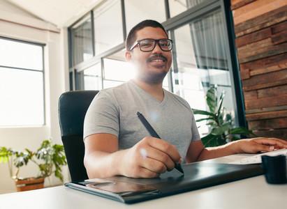Happy male designer working in office
