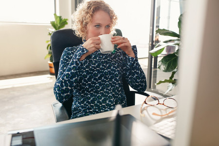 Thoughtful designer having coffee in office