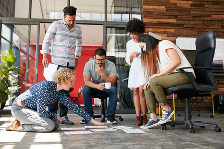 Creative people looking at project plan laid out on floor