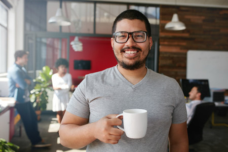 Smiling creative professional having coffee in office