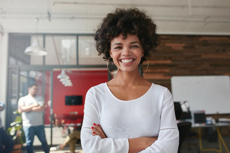 Smiling young woman standing in creative office