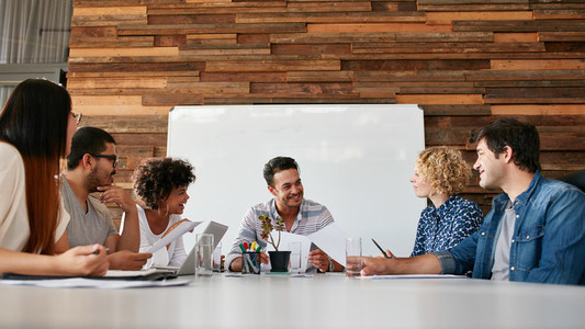 Happy young business people meeting in conference room