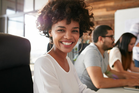 Cheerful african woman in conference room with coworkers