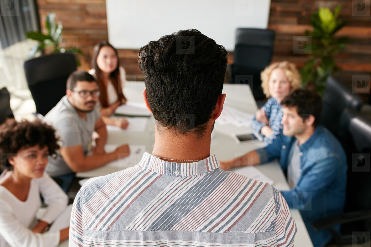 Man giving business presentation to colleagues in conference roo