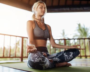 Woman meditating in lotus pose at health center
