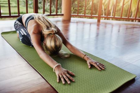 Young woman doing yoga on exercise mat