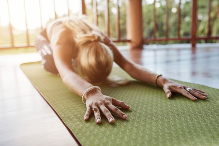 Fitness female performing balasana yoga at gym
