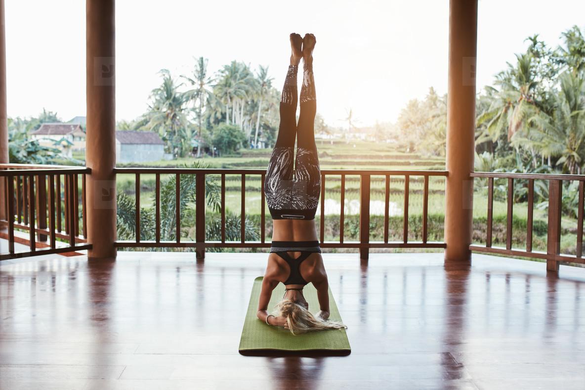 Fitness woman doing Sirsasana yoga
