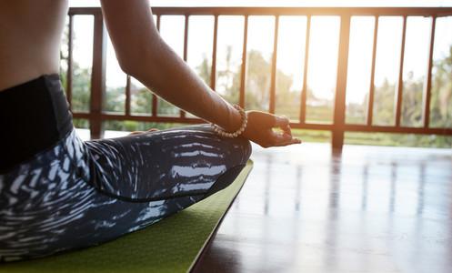 Female meditating in lotus pose at yoga class
