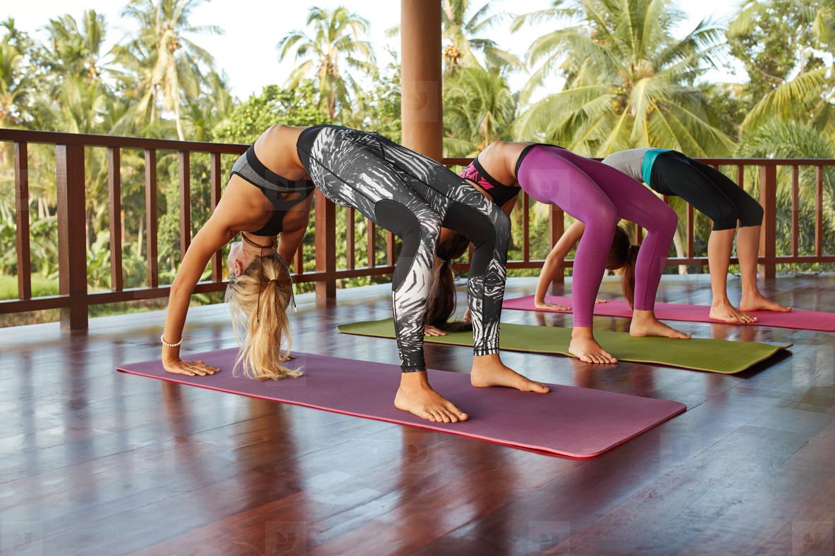 Women doing Chakrasana yoga  wheel pose