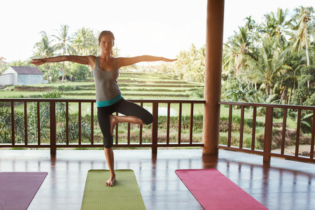 Fit young woman standing on one leg and meditating