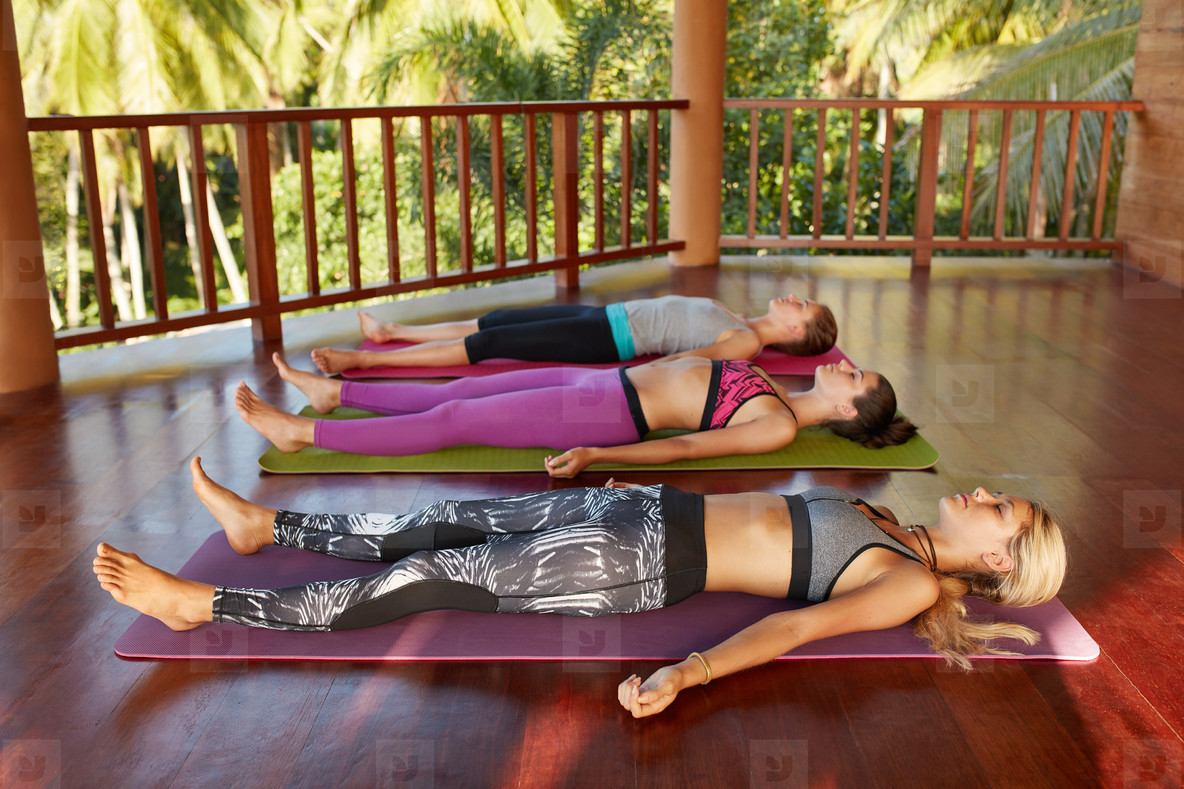 Yoga class with women lying on floor   Savasana