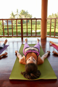 Fit young woman relaxing on yoga mat