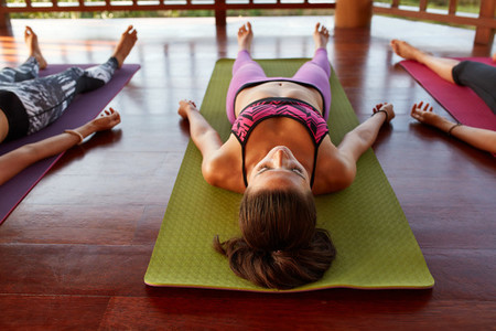 Young woman at yoga class doing savasana