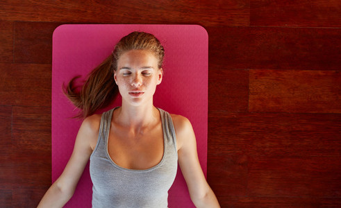 Fitness woman in corpse pose at gym