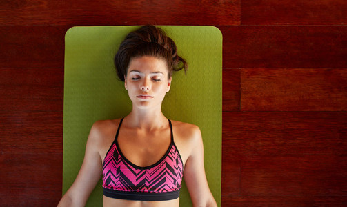 Healthy woman in savasana pose at gym