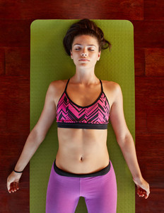 Healthy woman in savasana yoga pose at gym