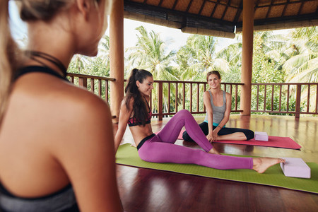 Female friends during yoga class break at fitness center
