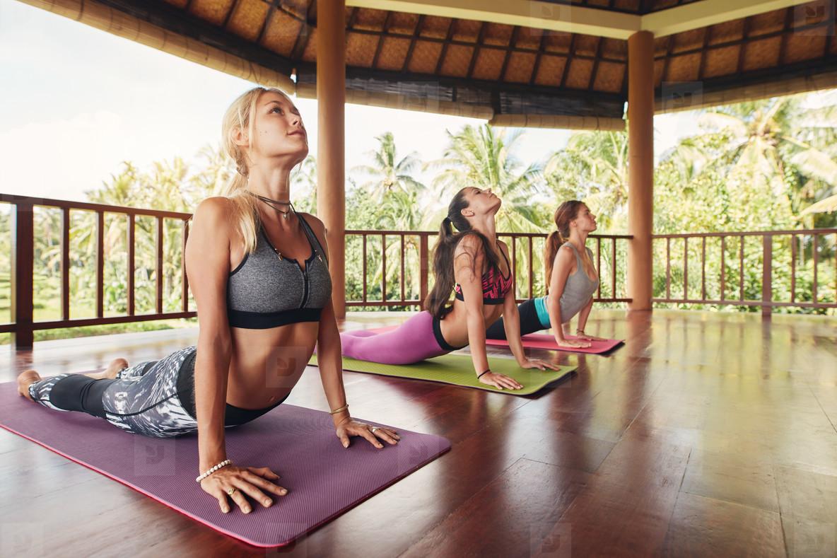 Women doing cobra pose at yoga class