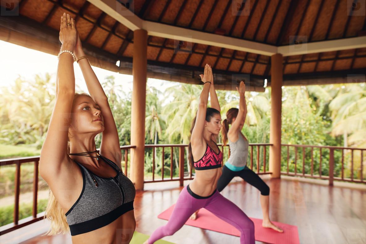 Group of young women doing Virabhadrasana asana