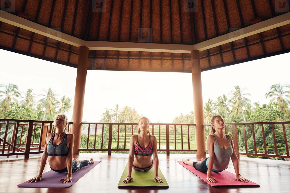 Three women doing the cobra pose yoga at class
