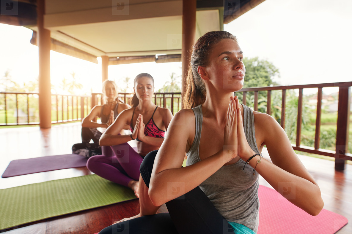 Young women practicing yoga in half spinal twist pose
