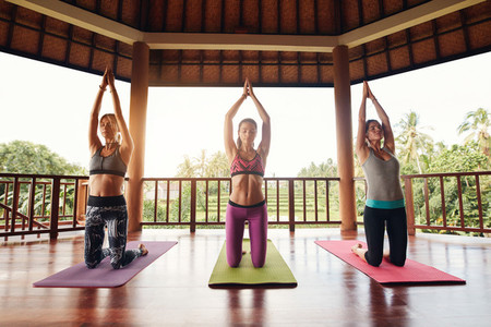Three young women doing yoga at health club