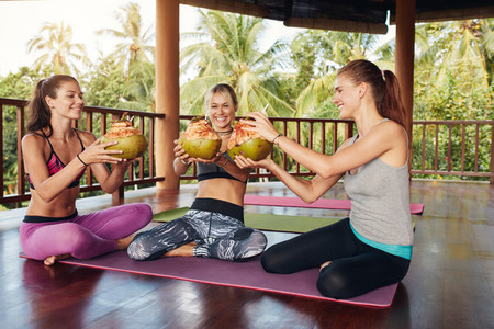 Women toasting green coconut at health club