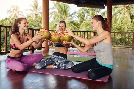Friends toasting green coconuts at yoga class