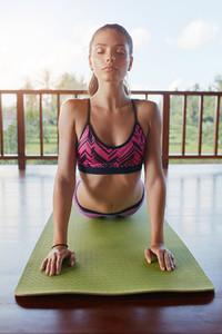 Fitness woman doing cobra pose yoga