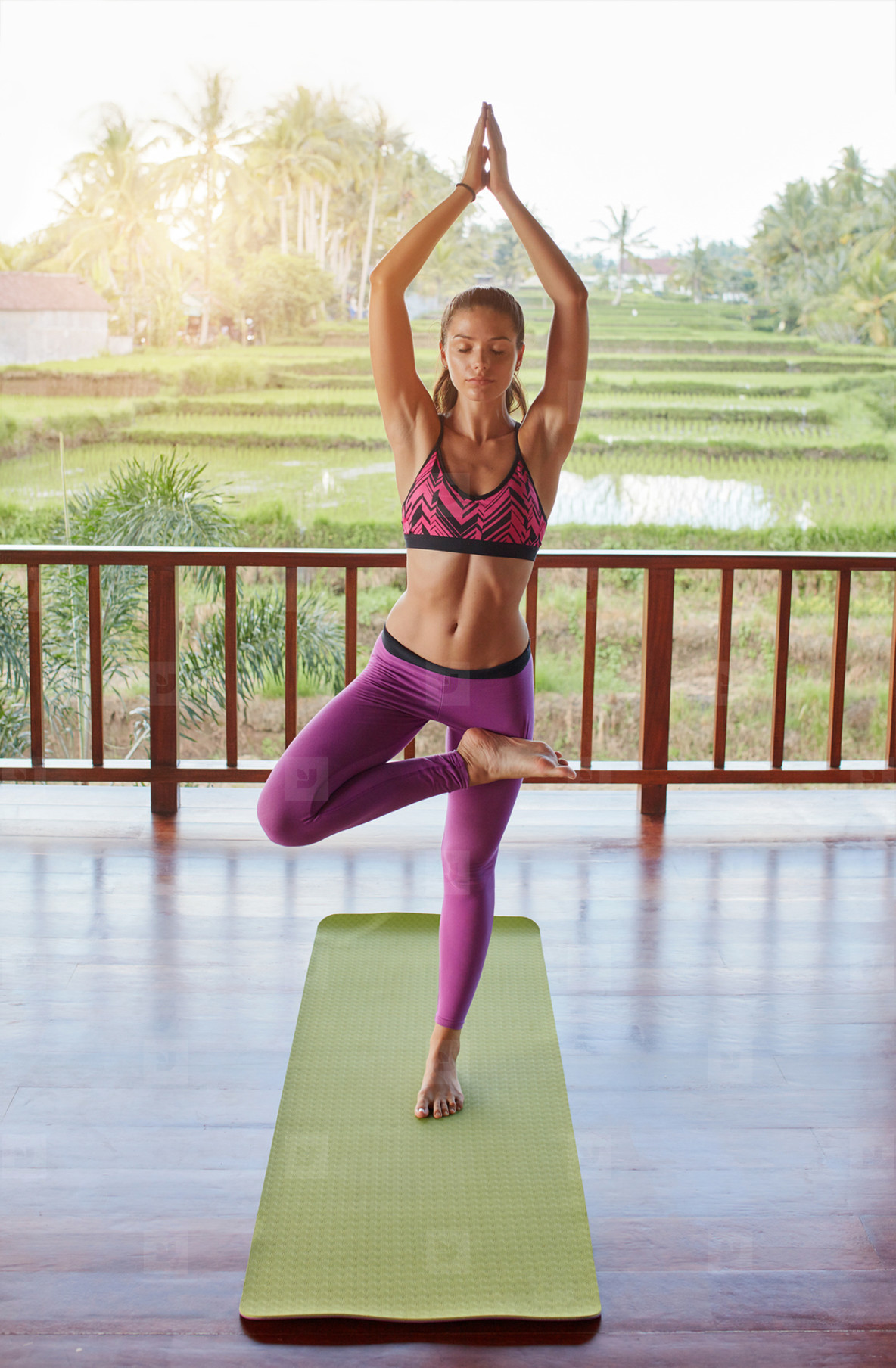 Young beautiful female doing yoga tree pose