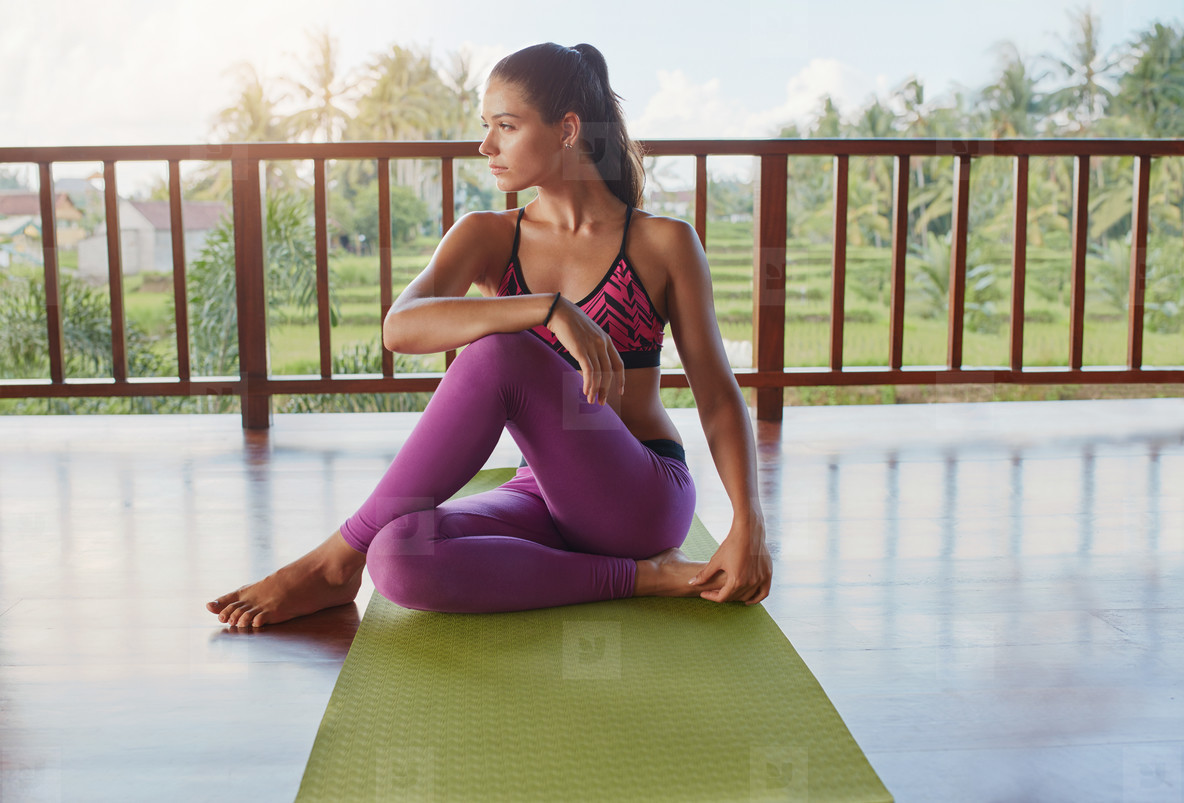 Woman sitting on yoga mat and looking away