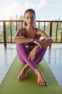 Young woman relaxing on yoga mat