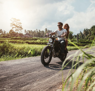 Couple riding motorcycle on country road