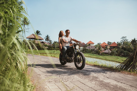 Young couple riding motorcycle on rural road