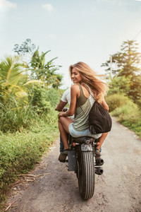 Young couple riding motorbike on dirt road