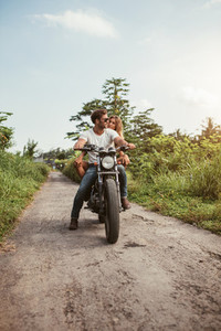 Couple on motorbike driving through dirt road