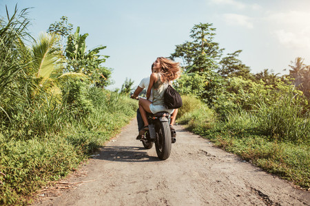 Couple riding motorcycle on rural road
