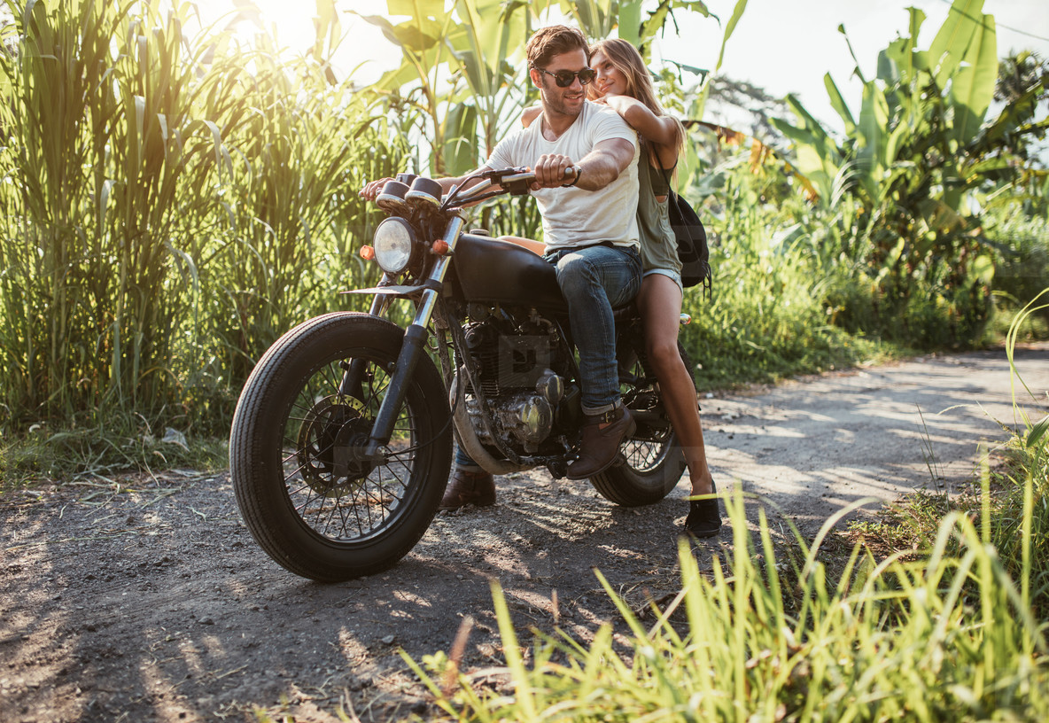 Young couple straddling motorbike on rural road